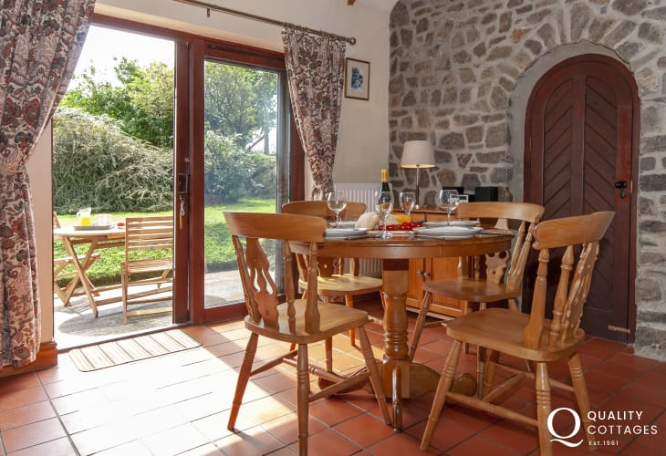 Self-catering Pembrokeshire holiday home - dining area with patio doors to gardens
