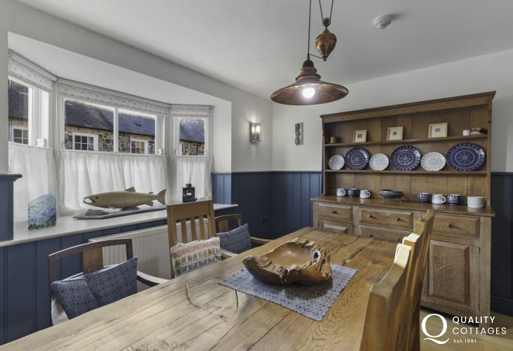 Panelled dining room with Welsh dresser, rectory table, chairs inside holiday cottage in Newport Pembrokeshire