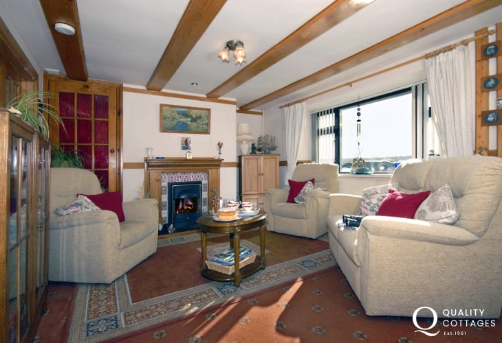 Haven Waterway Pembrokeshire holiday cottage - lounge with gas fire and stunning river views