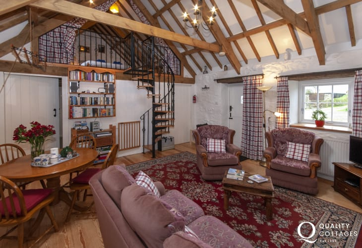 Traditional Welsh holiday cottage - living/dining room with spiral staircase to 'Crog Loft'