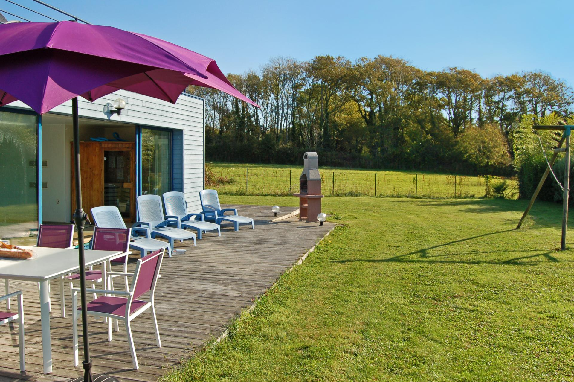 Sun loungers and table in garden, Annick, Brittany, Moelan-sur-mer.