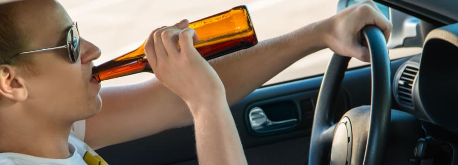 Man drinking beer while driving.