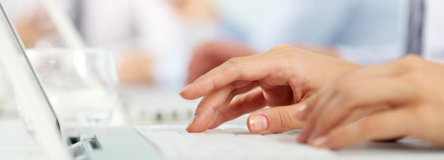 Close-up of female hands typing on the laptop keyboard
