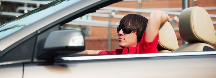 Young man driving a convertible car.