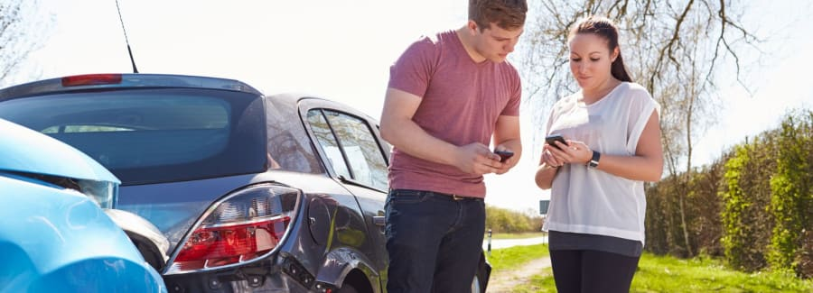Two people exchanging numbers after an accident.