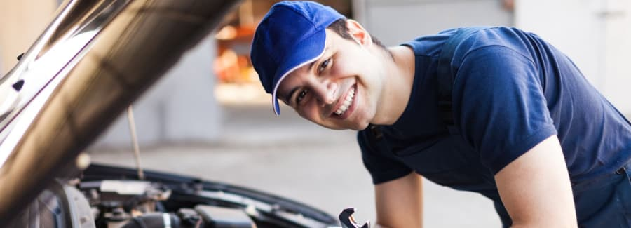 Young mechanic over open car smiling at camera while doing repairs.