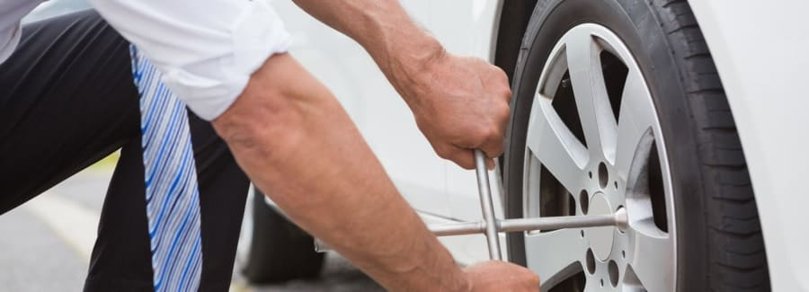 Man changing a tire, making car repair.