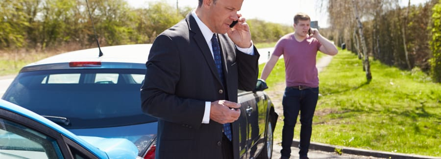 Businessman Making Phone Call After Traffic Accident