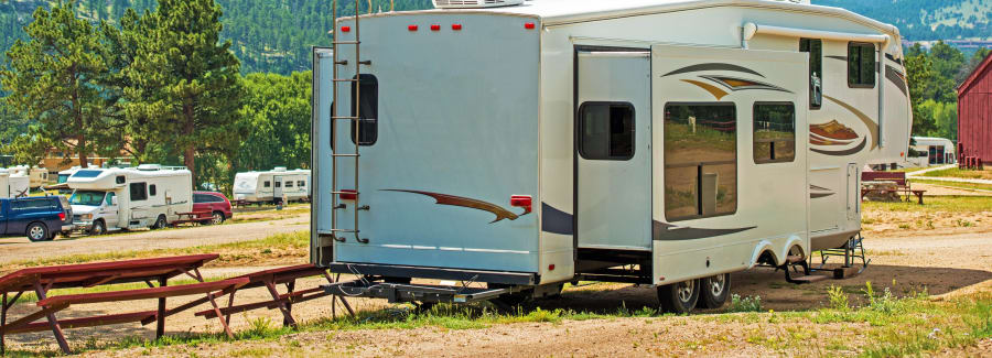 RV Fifth Wheel Camping. Travel Trailer with Extended Sliders in the Mountain Campground.