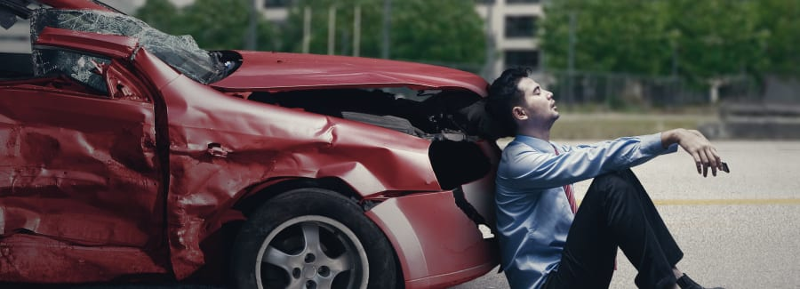 Image of stressful man sitting in front of a broken car after traffic accident on the road
