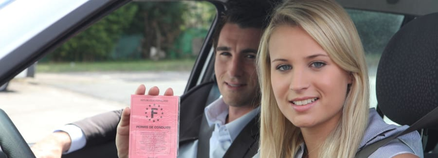 A blonde teenage girl with her learner's permit, sitting in the front seat of a car.