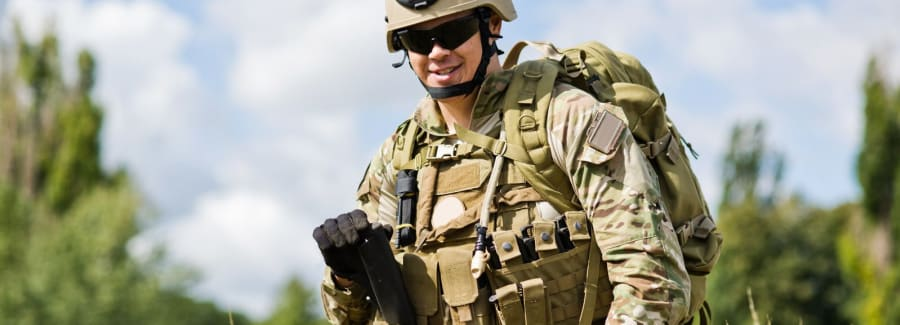 An American soldier stands in uniform , smiling at the camera.