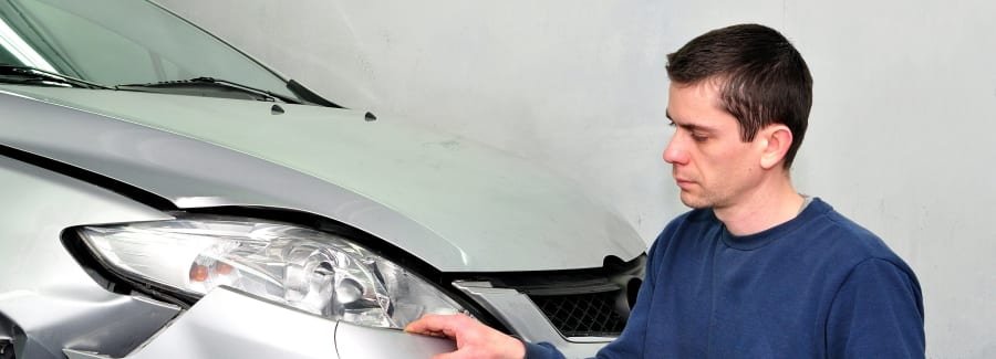 Insurance expert examining car damage.