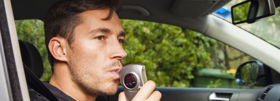 A man testing a breathalyzer.