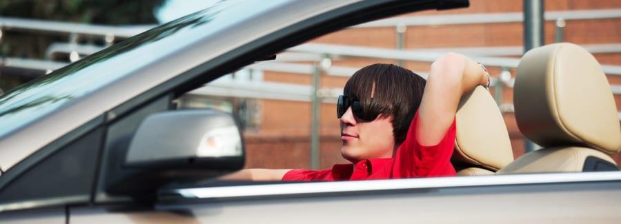 Young man driving a convertible car.