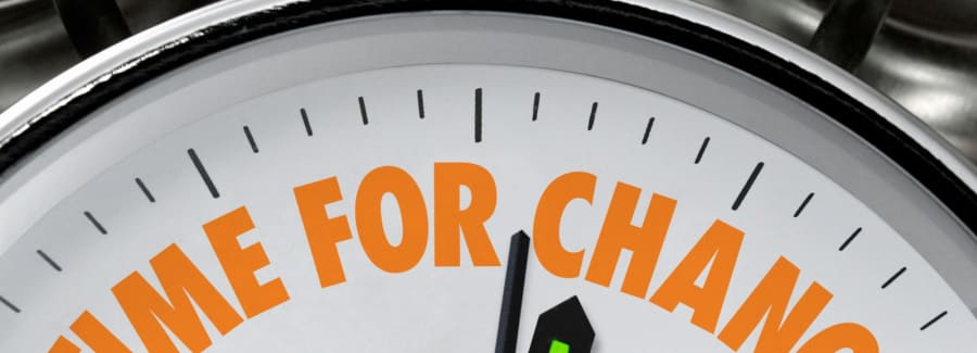"A clock with ""Time to Change!"" in orange lettering"