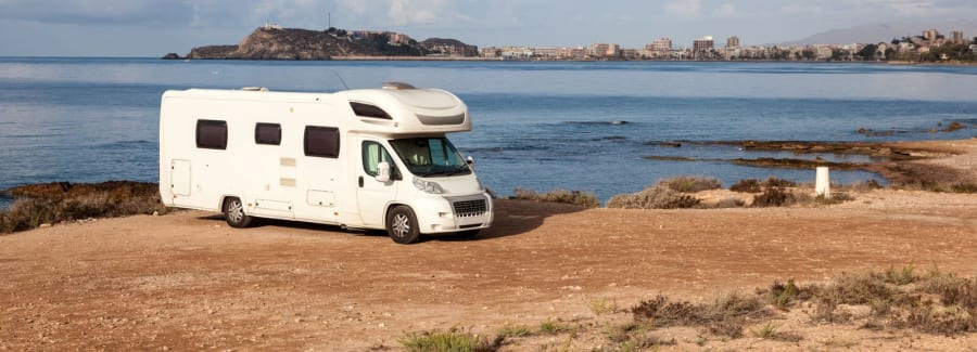 A motor home parked on a cliff overlooking the ocean.
