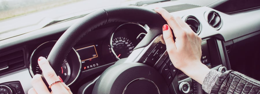 Close up image of female driver hands on the steering wheel. Red painted nails.
