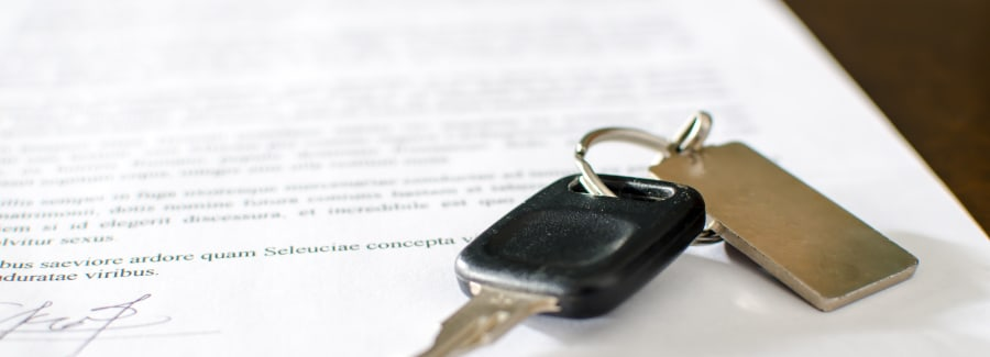 Car key on a signed sales contract, closeup