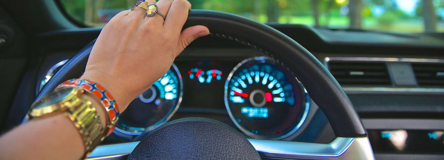 A woman driving with one hand on steering wheel.