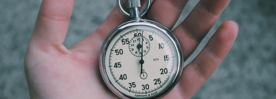 A hand holding a stop watch.