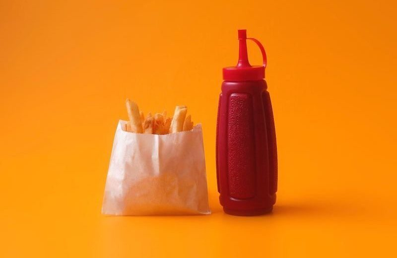 fries, ketchup bottle, orange background, white paper container