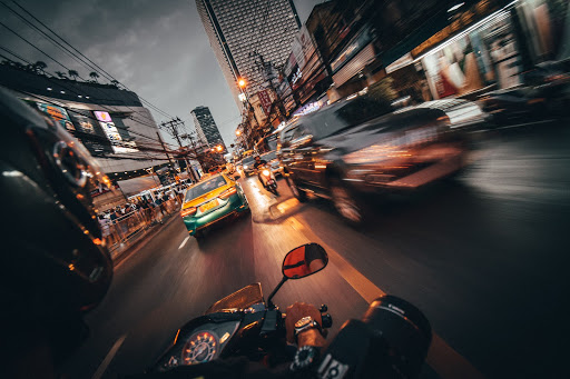 blurred view of street from motorcycle, yellow taxi, black road, speedometer