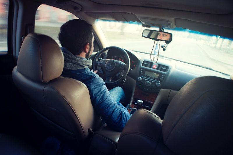 man driving car, tan interior, review mirror, steering wheel, dashboard, radio