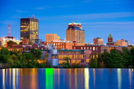 Manchester, New Hampshire skyline on the Merrimack River at night with lights on water