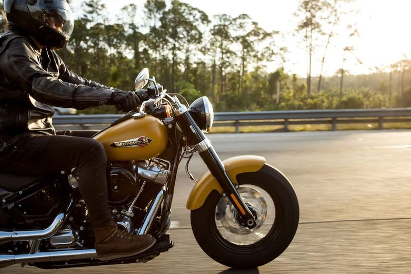 yellow motorcycle, scenic highway, black pants, boots, black jacket, black helmet