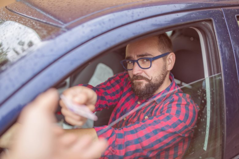 Man sitting in car and giving his driving licence through the window for a record check