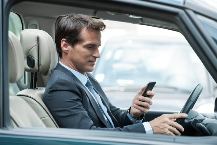 Man looking at cell phone while driving