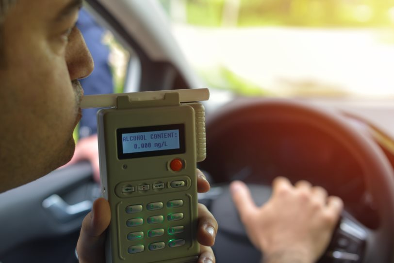 Driver being tested for alcohol content with use of breathalyzer