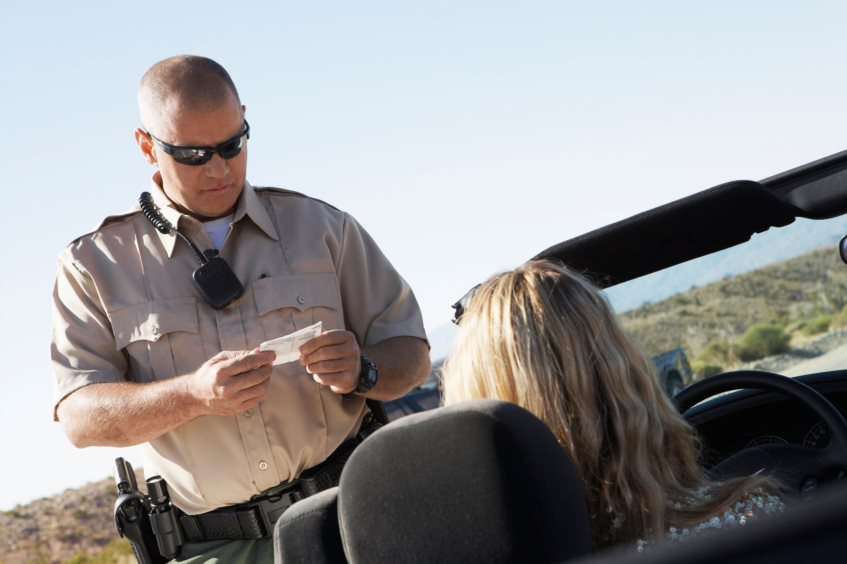 Woman in convertible receiving a traffic ticket from a police officer