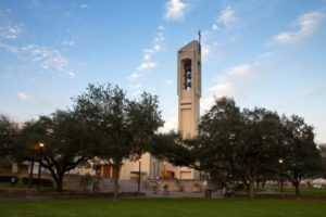 Church Bell Tower with cross in McAllen, Texas with green trees and blue sky