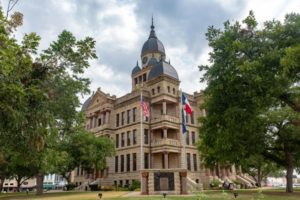 The historic 1896 Denton County courthouse in Denton, Texas with green trees