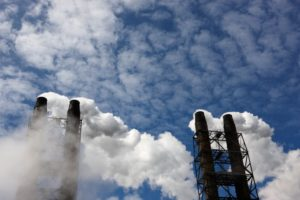 Industrial smoke stacks. Smoke pouring into air with blue sky backdrop