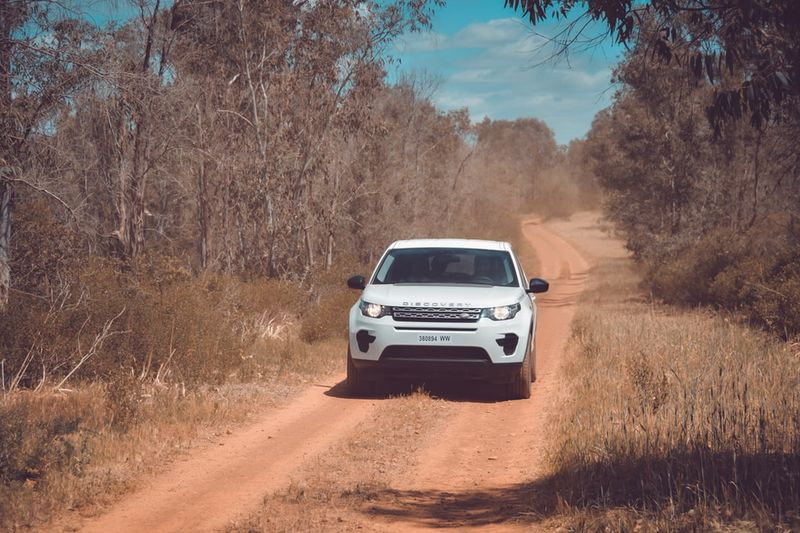 white SUV driving down dusty, orange clay road