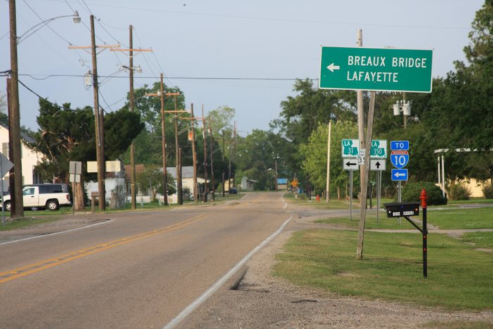 Rural road in southern Louisiana with signpost to Breaux Bridge and Lafayette