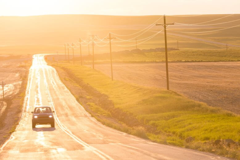 lone car on Montana road looking golden at early sunrise