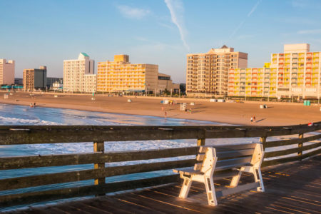 Dawn at Virginia Beach boardwalk in Virginia with bench and sun on buildings..