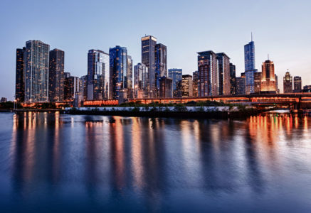 Chicago, Illinois skyline from the Navy Pier at sunset with building reflection on Lake Michigan.