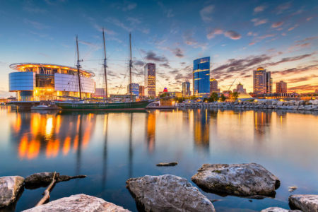 Downtown city skyline of Milwaukee, Wisconsin, USA on Lake Michigan with boat at twilight.