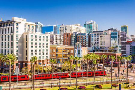 San Diego, California cityscape at the Gaslamp Quarter with palm trees and red trolly..