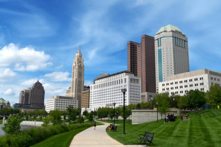 Columbus Ohio skyline on summer day with blue sky and green grass.