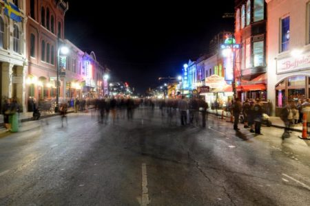 Sixth Street in Austin, Texas at night with people in the street.