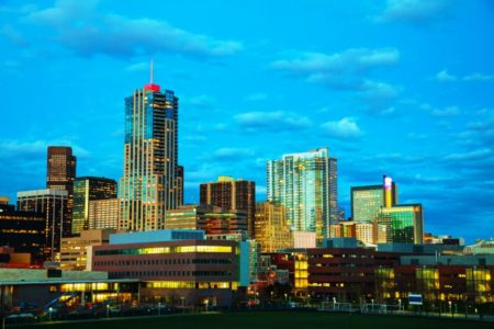 Downtown Denver, Colorado at the night with blue sky and city lights.