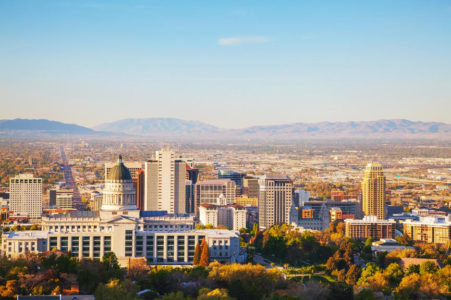 Salt Lake City, Utah panoramic overview with blue sky and mountains.