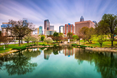 Charlotte, North Carolina skyline during summer with water and blue skies.