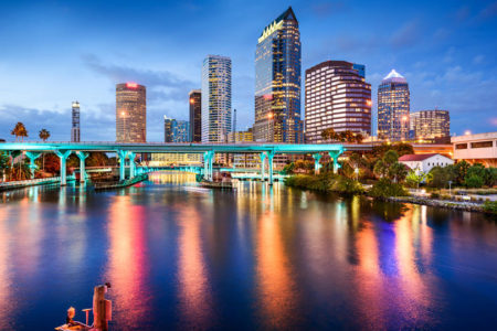 Downtown Tampa, Florida city skyline at dusk over the Hillsborough River with bridge and blue skies..